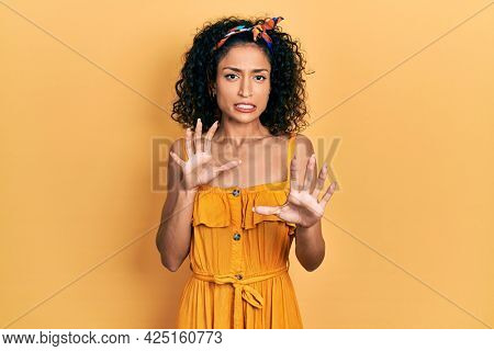 Young latin girl wearing summer dress disgusted expression, displeased and fearful doing disgust face because aversion reaction. with hands raised