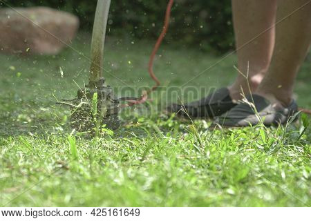 Grass Cutting. Man Using Grass Trimmer To Mow Lawn. Close Up, Defocused With Machine In Motion And G