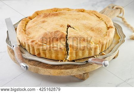 Ready Swiss Pie With Chard, Rice, Onions And Pine Nuts On A Wooden Stand On White Marble