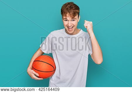 Young caucasian man holding basketball ball screaming proud, celebrating victory and success very excited with raised arms