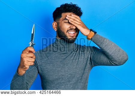 Arab man with beard holding pocket knife stressed and frustrated with hand on head, surprised and angry face
