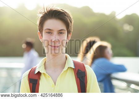 Young handsome 15 years old teen boy looking at camera and happy smiling over summer park in Kyiv, Europe