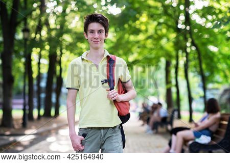 Young handsome 15 years old teen boy wearing yellow t-shirt with backpack looking at camera and happy smiling, summer park outdoor