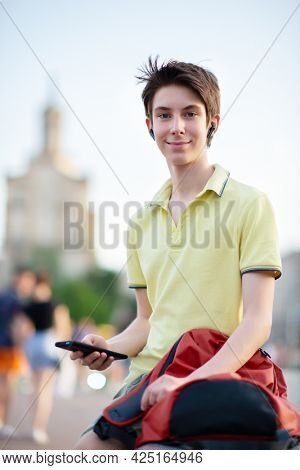 Young boy using smartphone over summer city outdoor. 15 years old teenager talking and sends messages by mobile phone, urban youth lifestyle