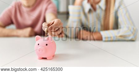 Young couple inserting coin inside piggy bank at home.