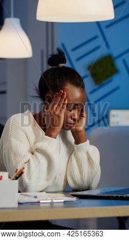 Overworked African Manager Woman Massaging Head While Sitting At Workplace In Start-up Office Workin