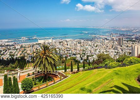 Israel. Gorgeous colorful gardens, flower beds, cypress trees and green lawns attract tourists. View from Mount Carmel to the international seaport of Haifa. Clear sunny day by the sea.
