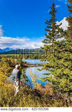 Elderly photographer - tourist photographing Pyramid Lake. Mount Pyramid is covered by lush cumulus clouds. Cold sunny day in the Rocky Mountains of Canada.