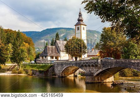 Magnificent alpine lake of glacial origin in the Julian Alps. Picturesque shores of Lake Bohinj. Slender bell tower and an old stone bridge. Slovenia, Central Europe