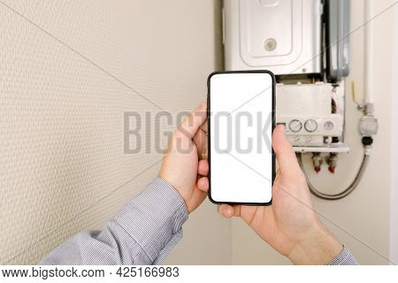 online diagnostics of household appliances via a mobile phone. a man repairing a boiler