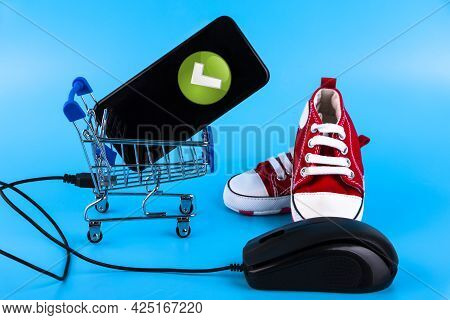 Online Store Of Children's Shoes, Red Sneakers On A Blue Background. Copy Space.