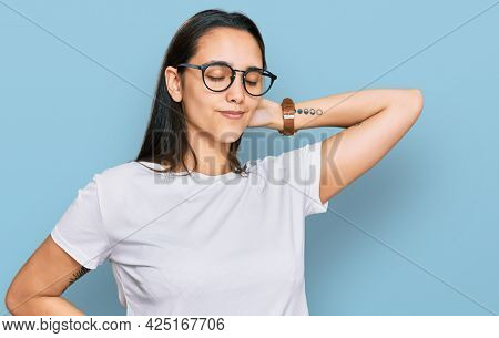 Young hispanic woman wearing casual white t shirt suffering of neck ache injury, touching neck with hand, muscular pain
