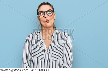 Young caucasian woman wearing business shirt and glasses making fish face with lips, crazy and comical gesture. funny expression.