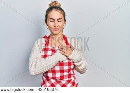 Beautiful caucasian woman with blond hair wearing apron smiling with hands on chest with closed eyes and grateful gesture on face. health concept.