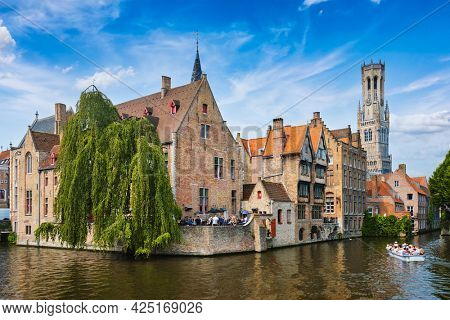 Famous view of Bruges tourist landmark attraction - Rozenhoedkaai canal with Belfry and old houses along canal with tree and tourist boat. Brugge, Belgium