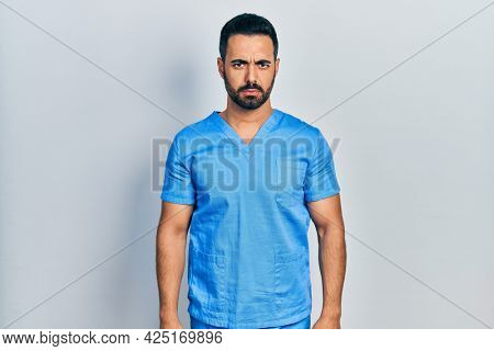 Handsome hispanic man with beard wearing blue male nurse uniform skeptic and nervous, frowning upset because of problem. negative person.