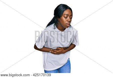 Young african american woman wearing casual white t shirt with hand on stomach because nausea, painful disease feeling unwell. ache concept.
