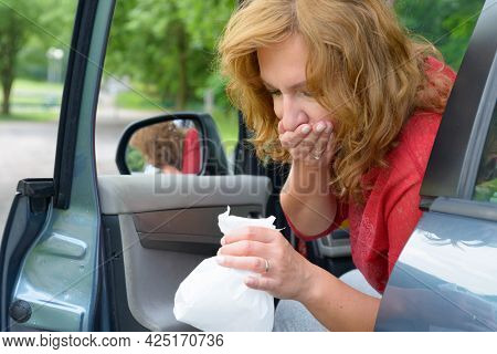 Woman suffering from motion sickness in a car and holding sick bag