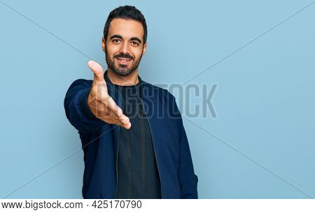 Young hispanic man wearing casual clothes smiling friendly offering handshake as greeting and welcoming. successful business.