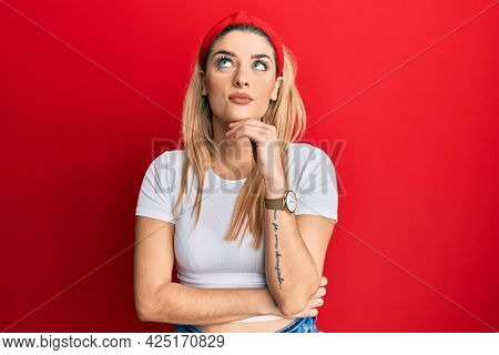 Young caucasian woman wearing casual white t shirt with hand on chin thinking about question, pensive expression. smiling and thoughtful face. doubt concept.