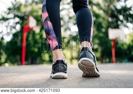 Closeup view on Young girl woman legs wearing sport leggings and shoes sneakers during exercising at stadium outdoors. Female person doing fitness workout outside