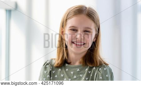 Closeup portrait of preteen beautiful blond hair girl in light room with blurred background. Female kid schoolgirl looking at the camera and smiling indoors
