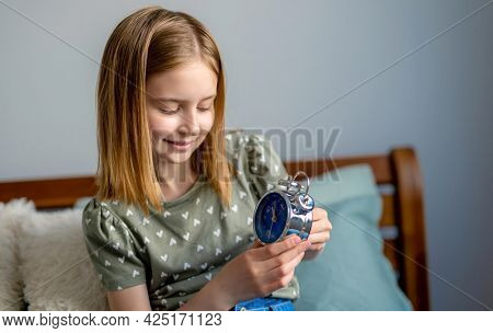 Portrait of preteen beautiful girl looking at metal clock with blue clockface in bedroom. Female kid schoolgirl sitting in the bed and turn on alarm