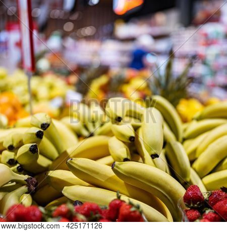 Colorful fruits and berries on farmer market closeup. Bananas and strawberry sold at grocery bazaar. Various healthy local and exotic raw food