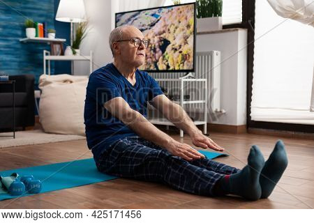 Senior Man Stretching Legs Muscle While Sitting On Yoga Mat In Living Room During Pilates Workout. P