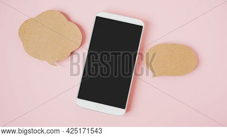 White Smart Phone With Clipping Path On Touchscreen , Couple Of Speech Bubbles  Paper On Sweet Pink