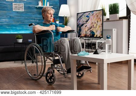 Invalid Senior Woman In Wheelchair Training Body Muscles Using Gymnastic Dumbbells Recovery After Pa