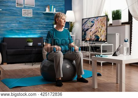 Focused Senior Woman In Sportswear Watching Online Fitness Workout On Tablet Sitting On Swiss Ball E