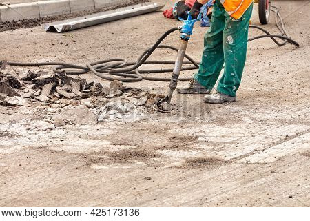 A Road Worker In Green Overalls Loosens Old Asphalt With A Pneumatic Jackhammer On The Road On A Sum