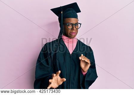 Young african american girl wearing graduation cap and ceremony robe disgusted expression, displeased and fearful doing disgust face because aversion reaction.
