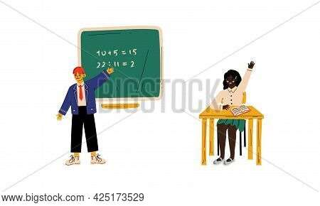 Clever Girl Sitting At Desk At School Lesson And Raising Her Hand To Answer And Boy Standing At Blac