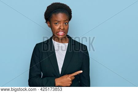 Young african american girl wearing business clothes pointing aside worried and nervous with forefinger, concerned and surprised expression
