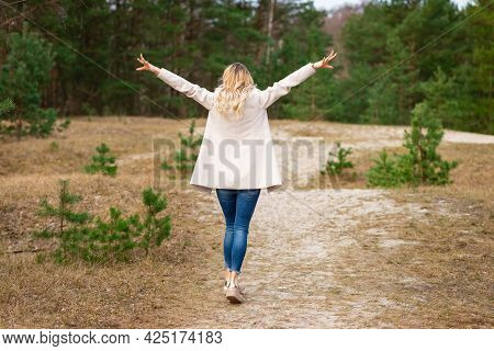 One Young Beautiful Blonde Long Haired Woman Standing Backwards And Raised Hands Over Green Backgrou