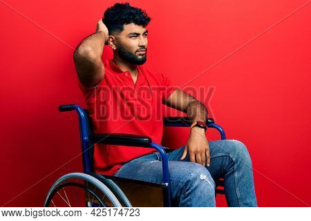 Arab man with beard sitting on wheelchair confuse and wondering about question. uncertain with doubt, thinking with hand on head. pensive concept.
