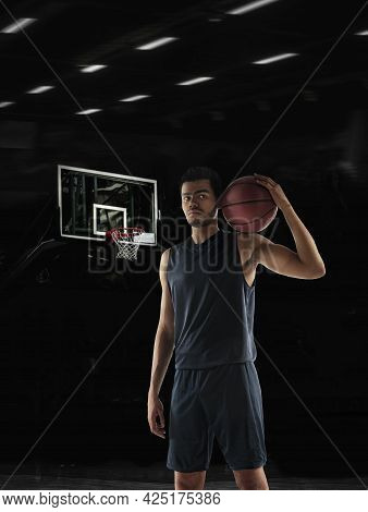 Portrait Of Young African Sportsman, Basketball Player Posing In Gym, Idoors Isolated On Dark Backgr