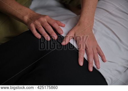 A Woman Does A Holistic Back Massage On A Home Bed In The Bedroom. Masseuse On The Couch Massages A