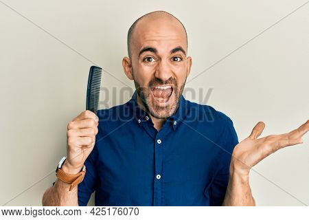 Young hispanic man holding comb loosing hair celebrating victory with happy smile and winner expression with raised hands
