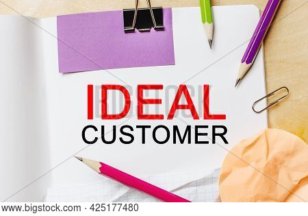 Text Ideal Customer On A White Notepad With Pencils On A Wooden Background. Business Concept