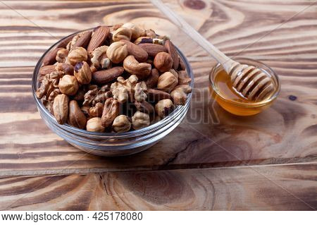 Assorted Nuts In Glass Bowl With Honey Bowl And Honey Dipper. Mixed Nuts On Wooden Table. Black Ston