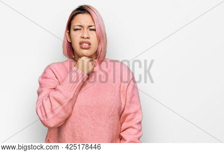 Hispanic woman with pink hair wearing casual winter sweater touching painful neck, sore throat for flu, clod and infection