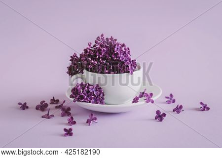White Cup With Blossoming Lilac On A Purple Pastel Background.  Flat Lay. Place For Text.