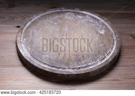 Pizza cutting board and wheat powder flour for homemade bread cooking or baking on table. Wooden tabletop background. Bakery concept in kitchen