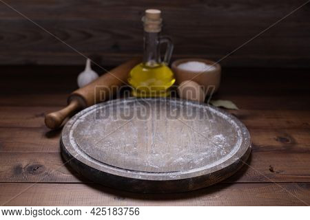 Pizza cutting board and food ingredient with wheat powder flour for homemade bread cooking or baking on table. Wooden tabletop background. Bakery concept in kitchen