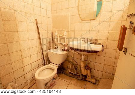 A Dirty Old Toilet With A Special Atmosphere, Everything Is Rusty And Unusable.