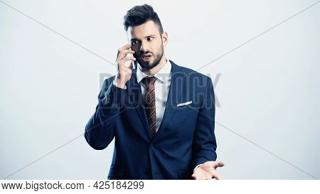 Discouraged Businessman Gesturing While Talking On Cellphone Isolated On White