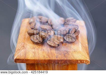 Aromatic Coffee Beans In Hot Steam Close-up On Dark Background. Aroma Of Coffee